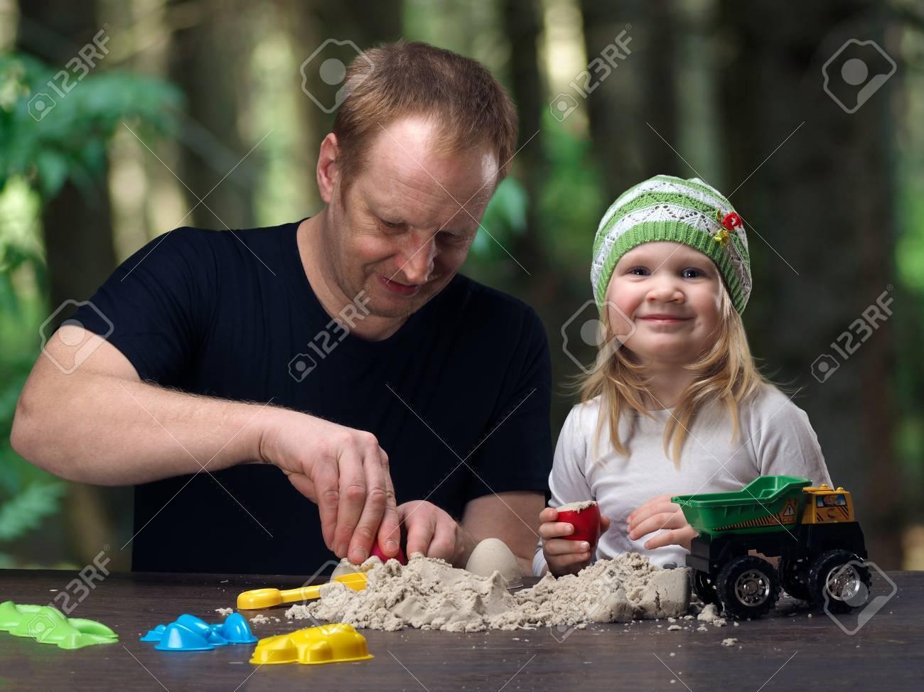 Pequena Hija Y Padre Jugando En La Arena En La Casa De Campo Calor