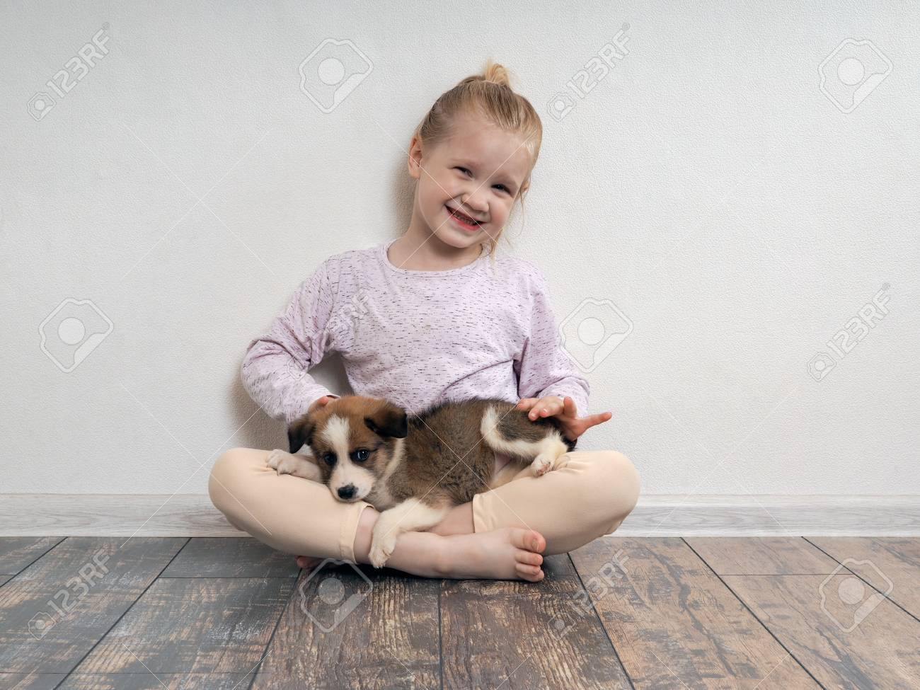Happy Girl With Puppy On Her Lap The Child Sits On The Floor