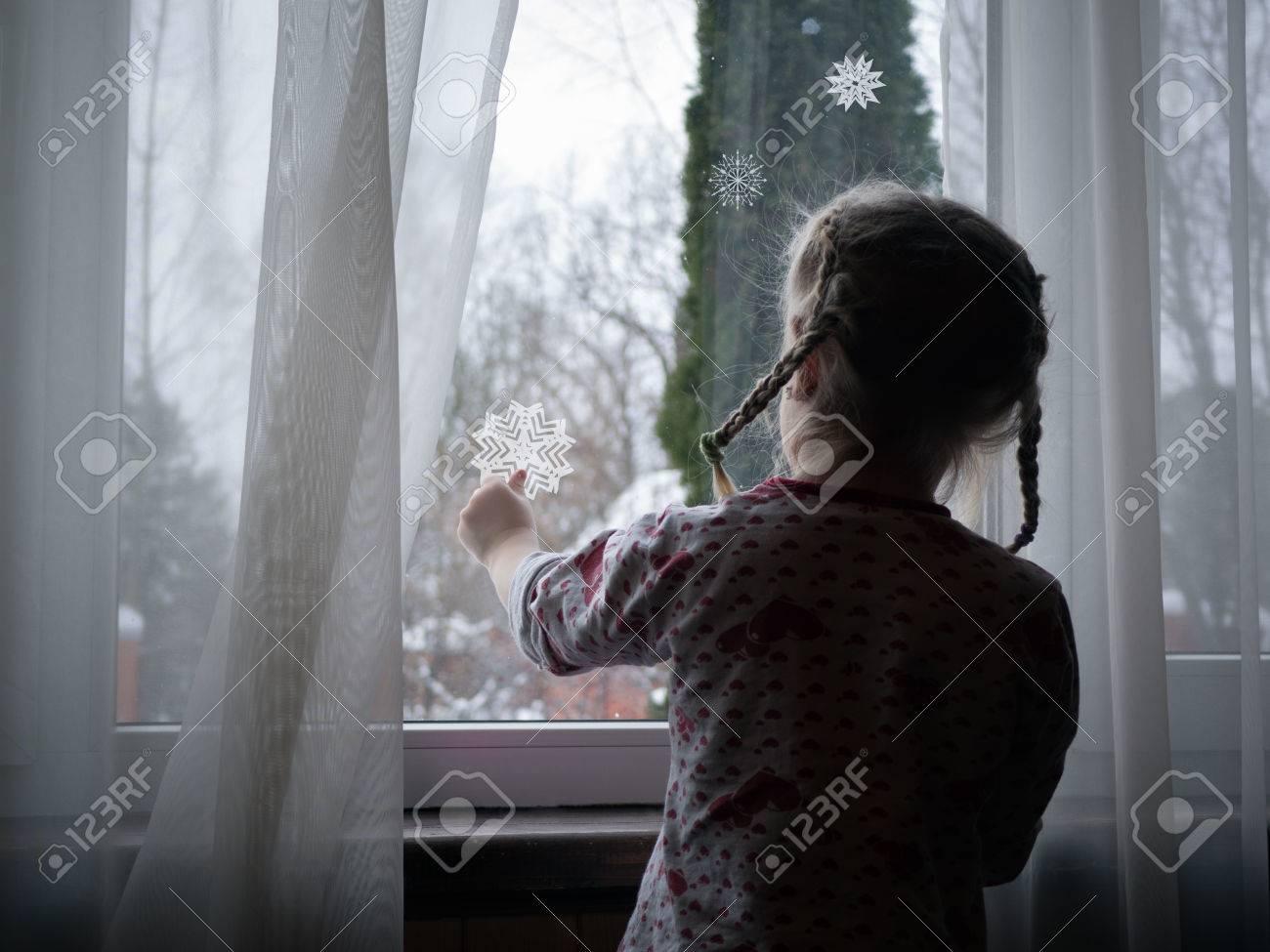 Fiocchi Di Neve Di Carta Modelli : Bambina decorata la finestra incolla i fiocchi di neve di carta