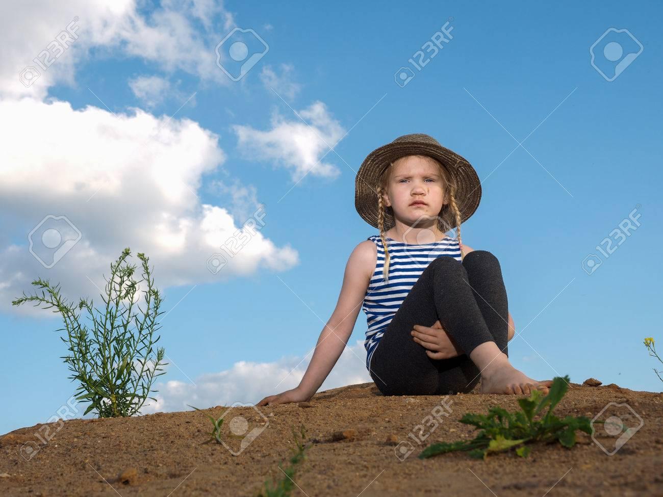 Archivio Fotografico - Il bambino è seduto su una montagna di sabbia. Cielo  blu. Una bambina 0dadb80980fe