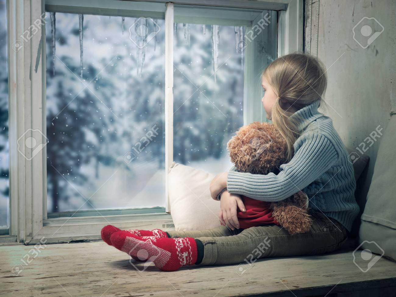 Little girl looking out the window. Outside, the winter snow. - 90279499