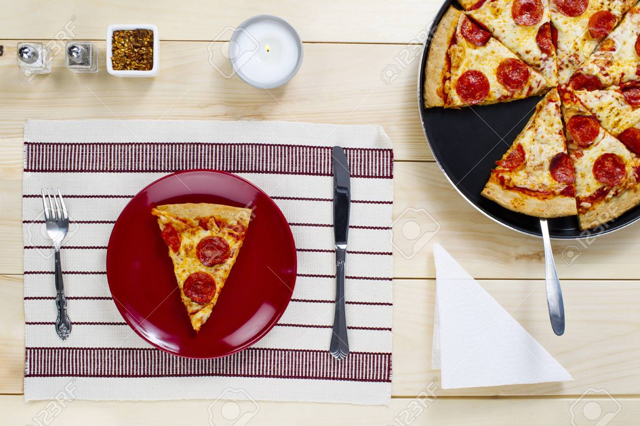 Slice of pizza on plate with pizza on pan on wooden board Stock Photo - 15840089