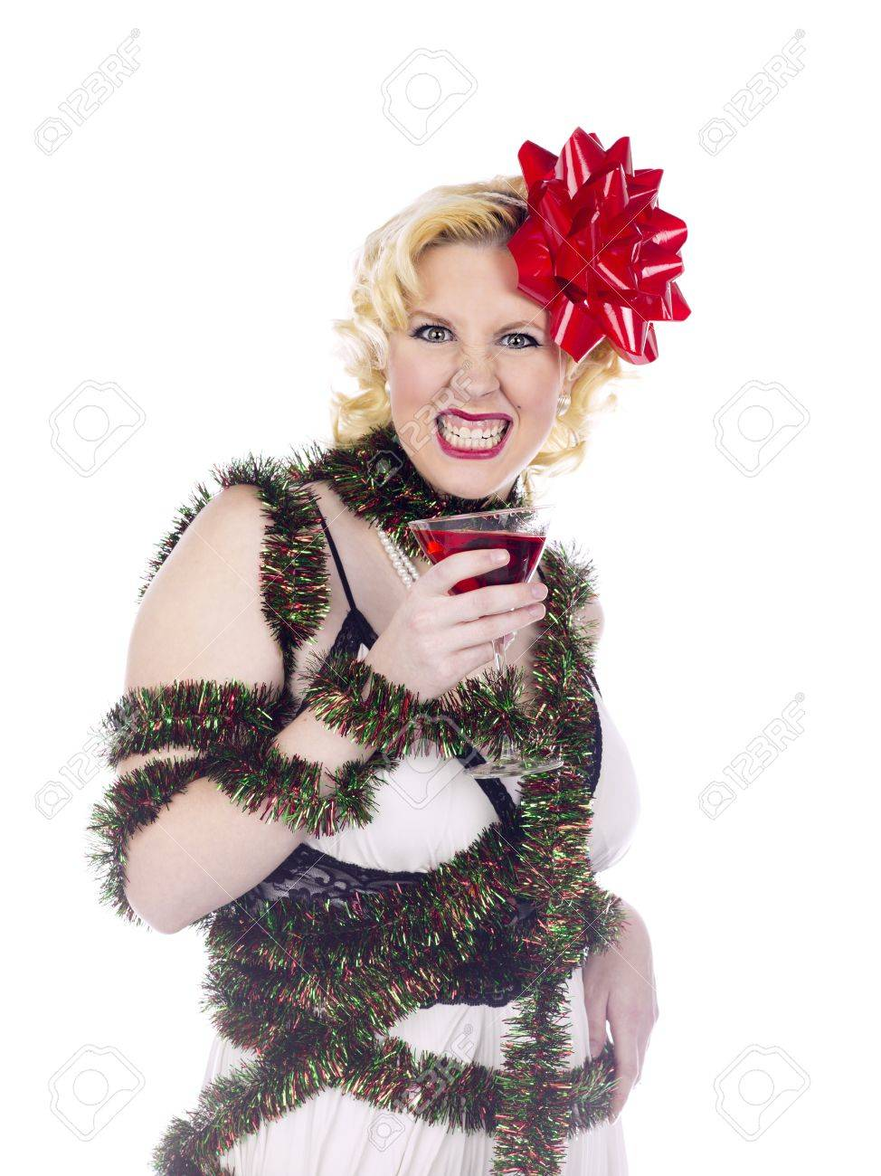 Woman draped in Christmas decorations and holding a martini glass makes a funny face on white Stock Photo - 16973898