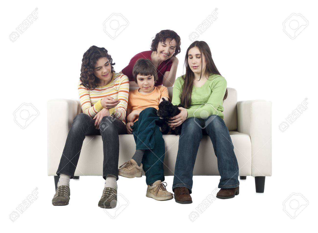 Portrait of a happy family in the living room sofa playing with their pet puppy Stock Photo - 17071110