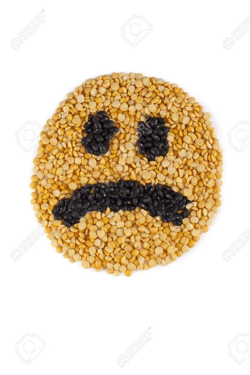 Una imagen del primer plano de la cara triste hecha de los granos de color amarillo y negro sobre un fondo blanco Foto de archivo - 16996699