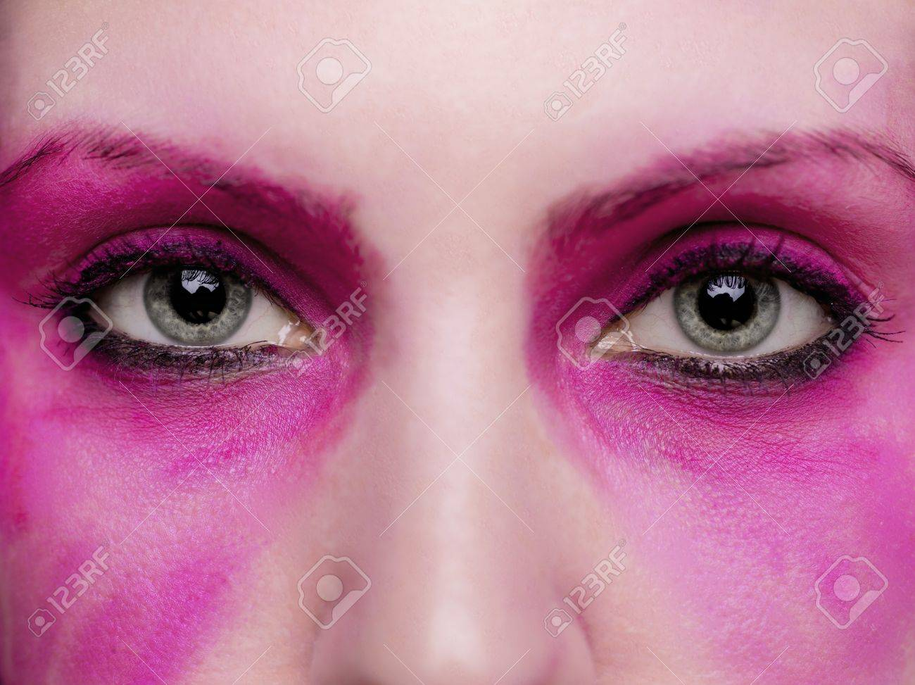 A close up on a pair of eyes surrounded by hot pink make up. Stock Photo - 17134439