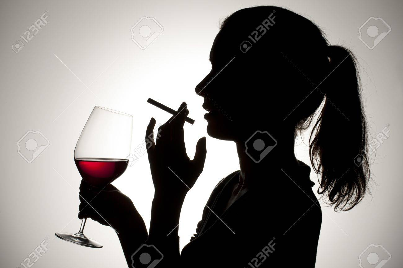 Silhouette shot of a female smoking a cigarette and holding a red wine glass. Stock Photo - 17134671