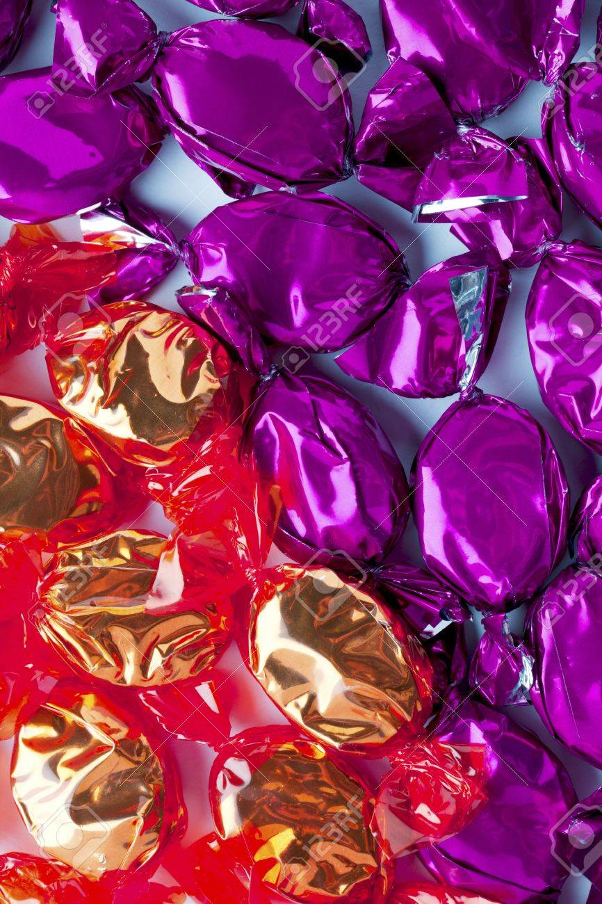 Close-up shot of hard candies wrapped in shiny golden and purple candy wrapper. Stock Photo - 17135277