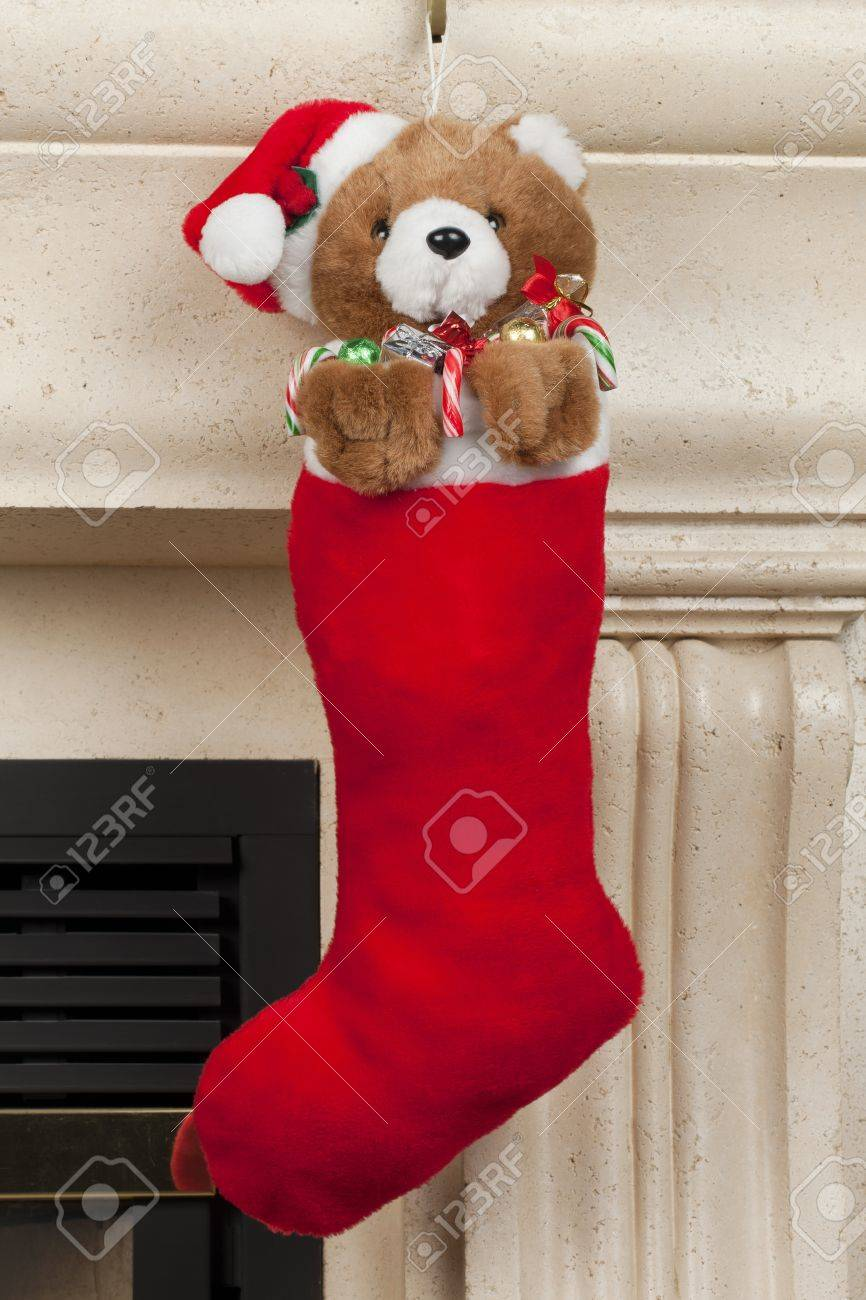 Bear Christmas Stocking.A Brown Teddy Bear Hanging Over The Red Christmas Stocking