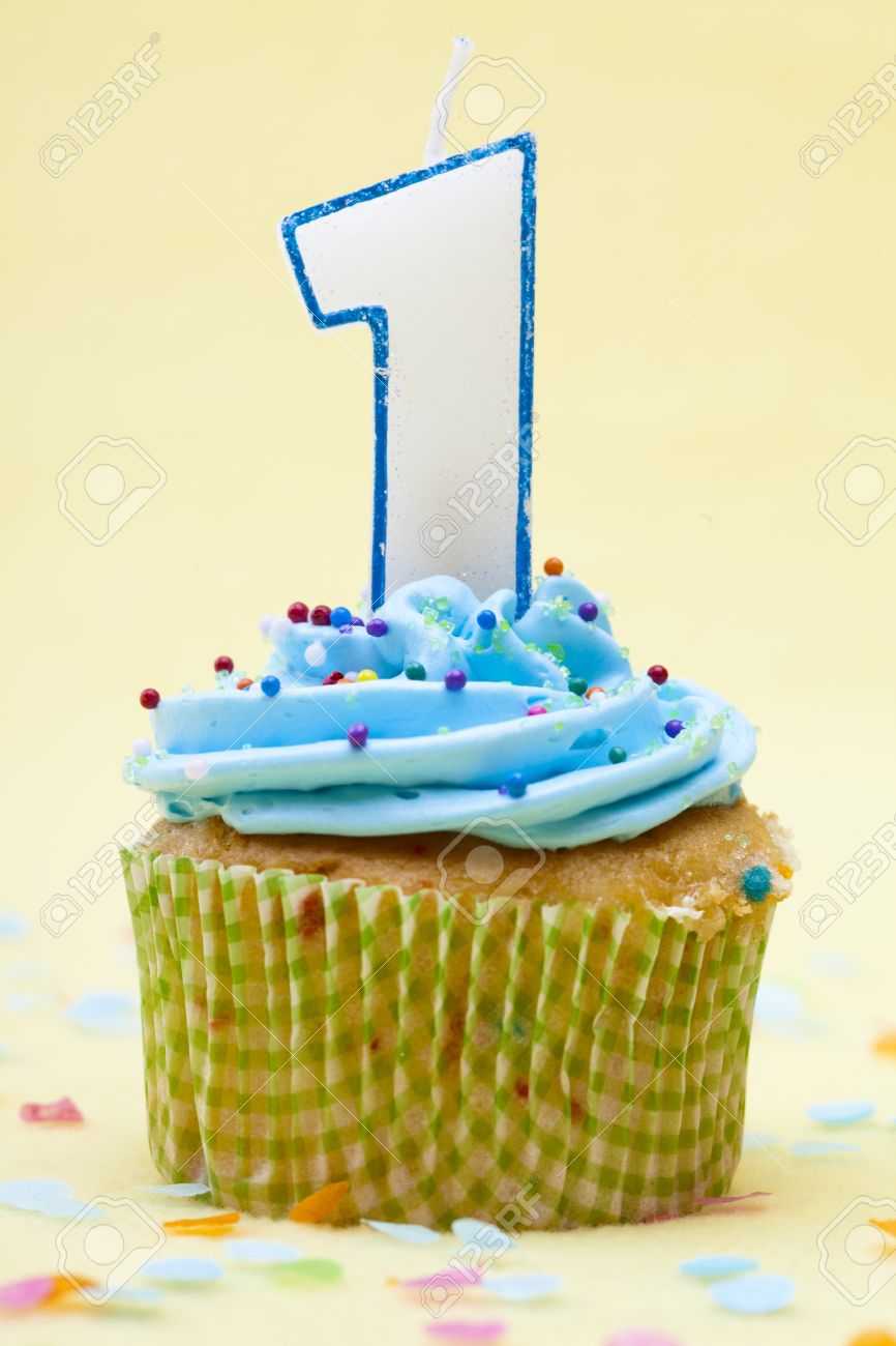 Close Up Shot Of A Cupcake With Number 1 Birthday Candle Over Yellow Background