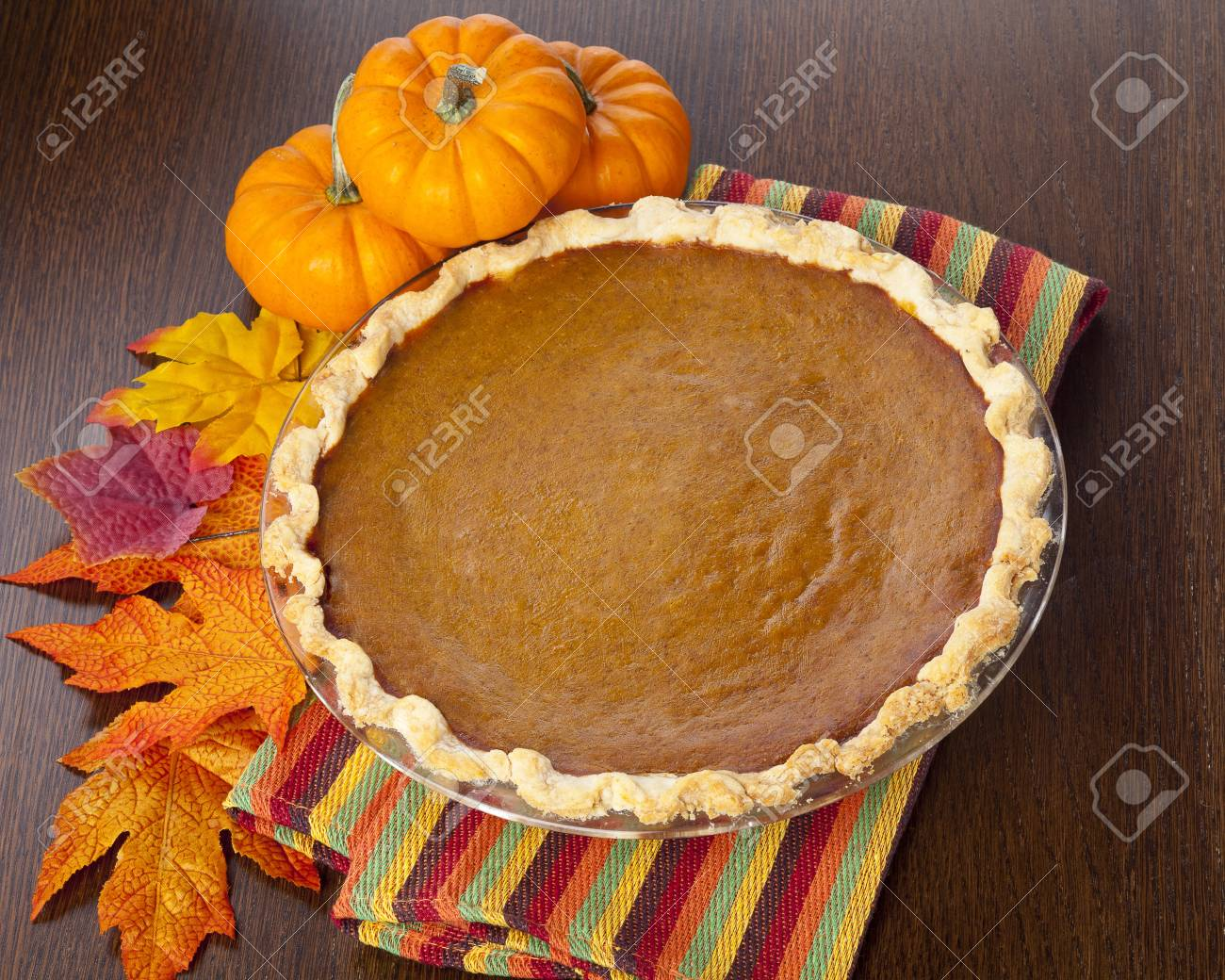 Pie on a wooden table, sitting next to pumpkins and leaves. Stock Photo - 17210488