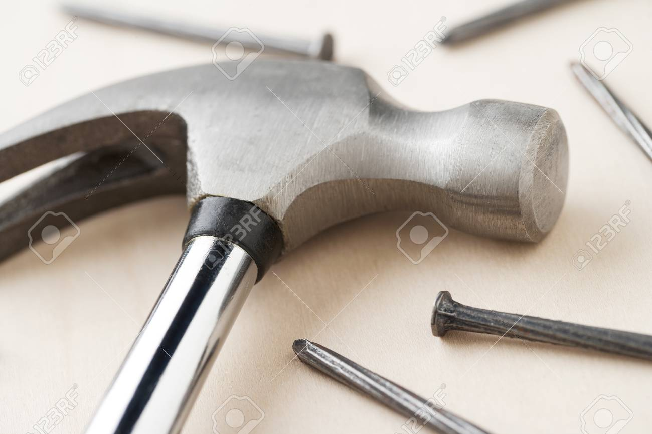 A close-up shot of hammer's head and concrete nail on a wooden table Stock Photo - 17251366