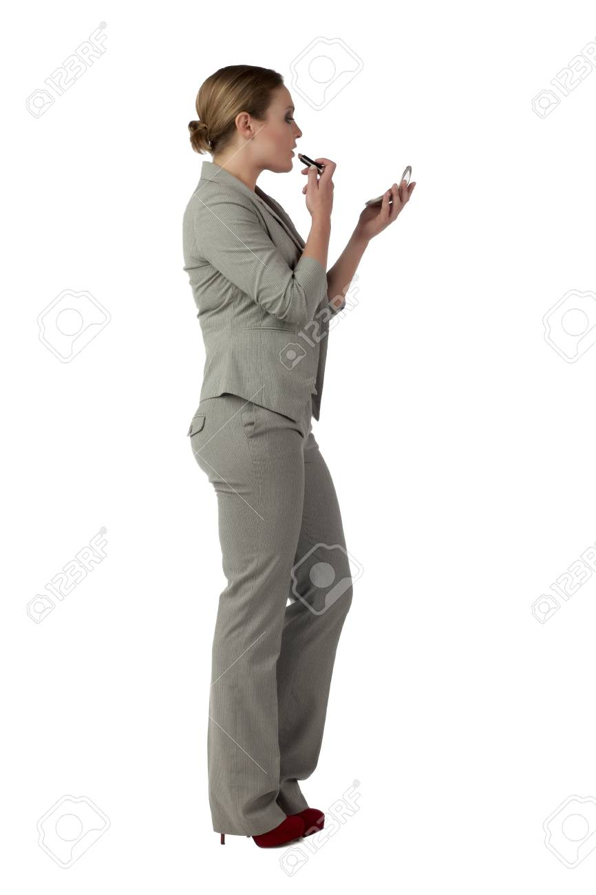 Portrait of businesswoman applying make up against white background Stock Photo - 17351588