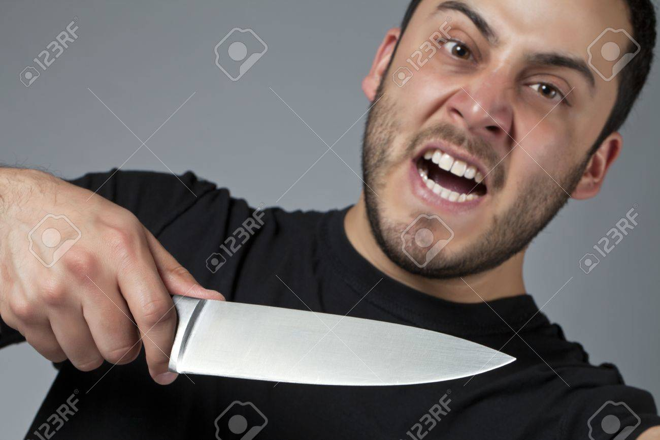 Close-up image of an angry male killer holding a knife over the gray background Stock Photo - 17377426