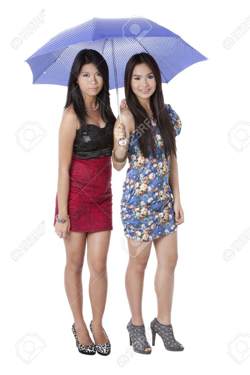 Portrait Of Two Gorgeous Ladies Sharing An Umbrella Over A White