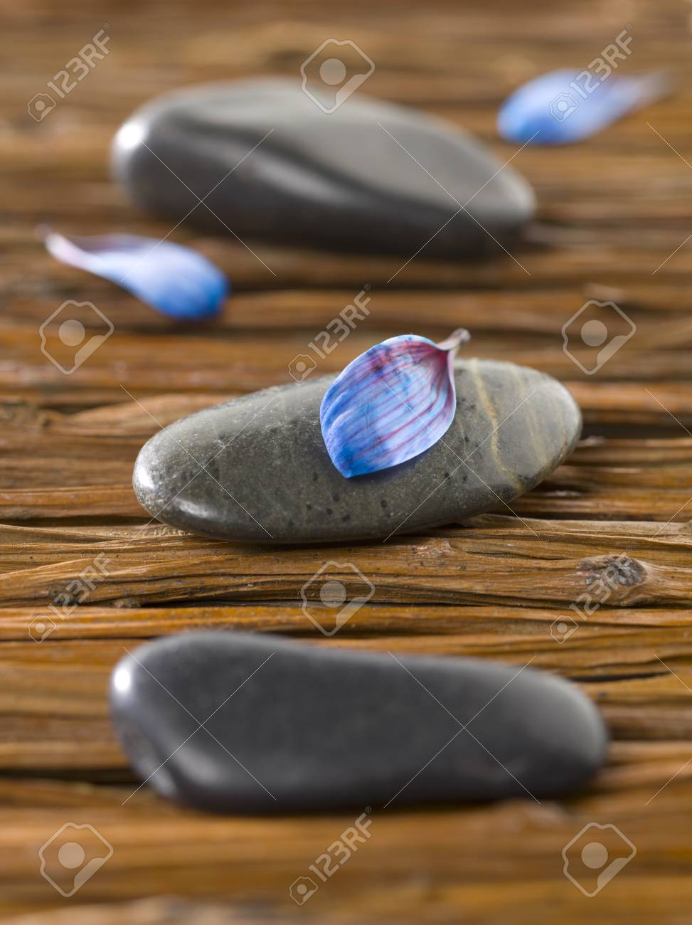 Closeup shot of spa stones with blue petals lying on a weave wooden background Stock Photo - 17489076