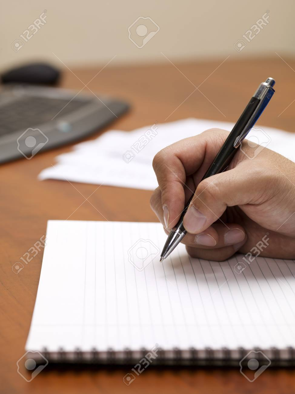 Close-up image of human hand writing on spiral writing pad on wooden desk. Stock Photo - 17496225