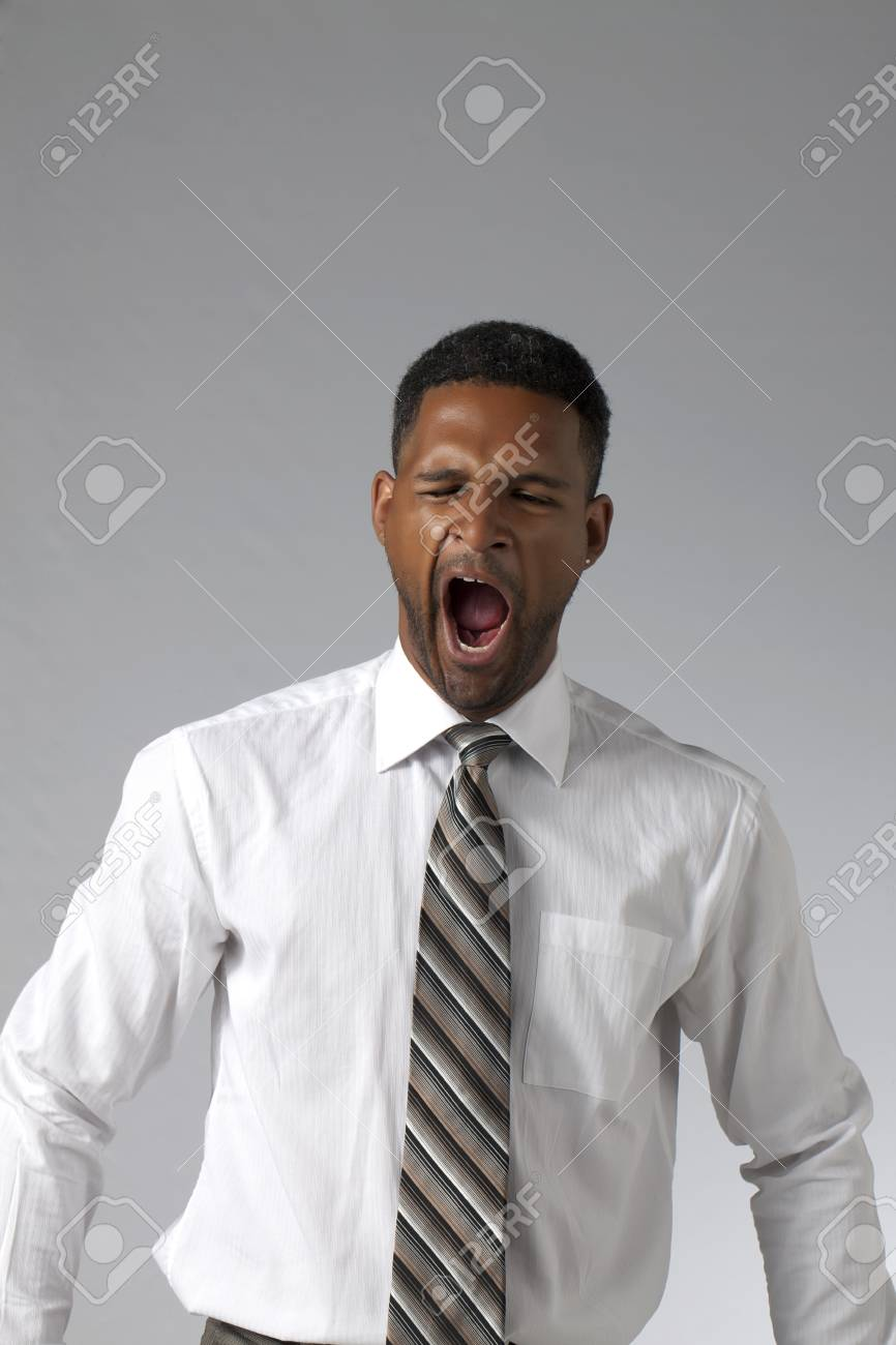 Portrait of black businesman yawning against a grey background Stock Photo - 17519201