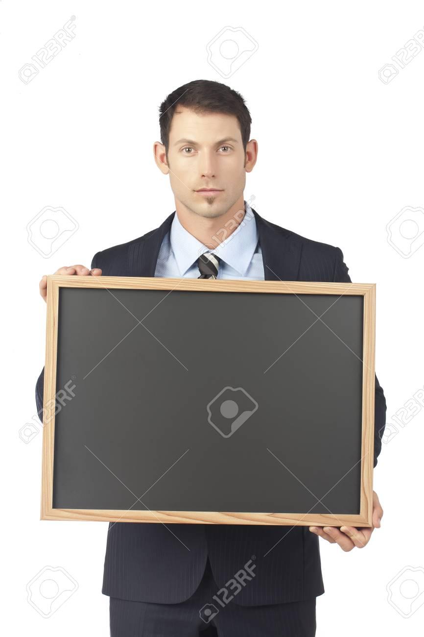 Serious businessman holding a blackboard Stock Photo - 17518920