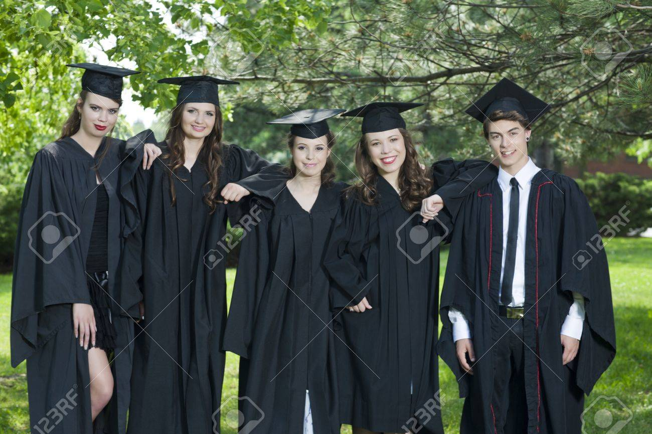 Group Of Successful Students With Caps And Gowns Taking A Picture ...