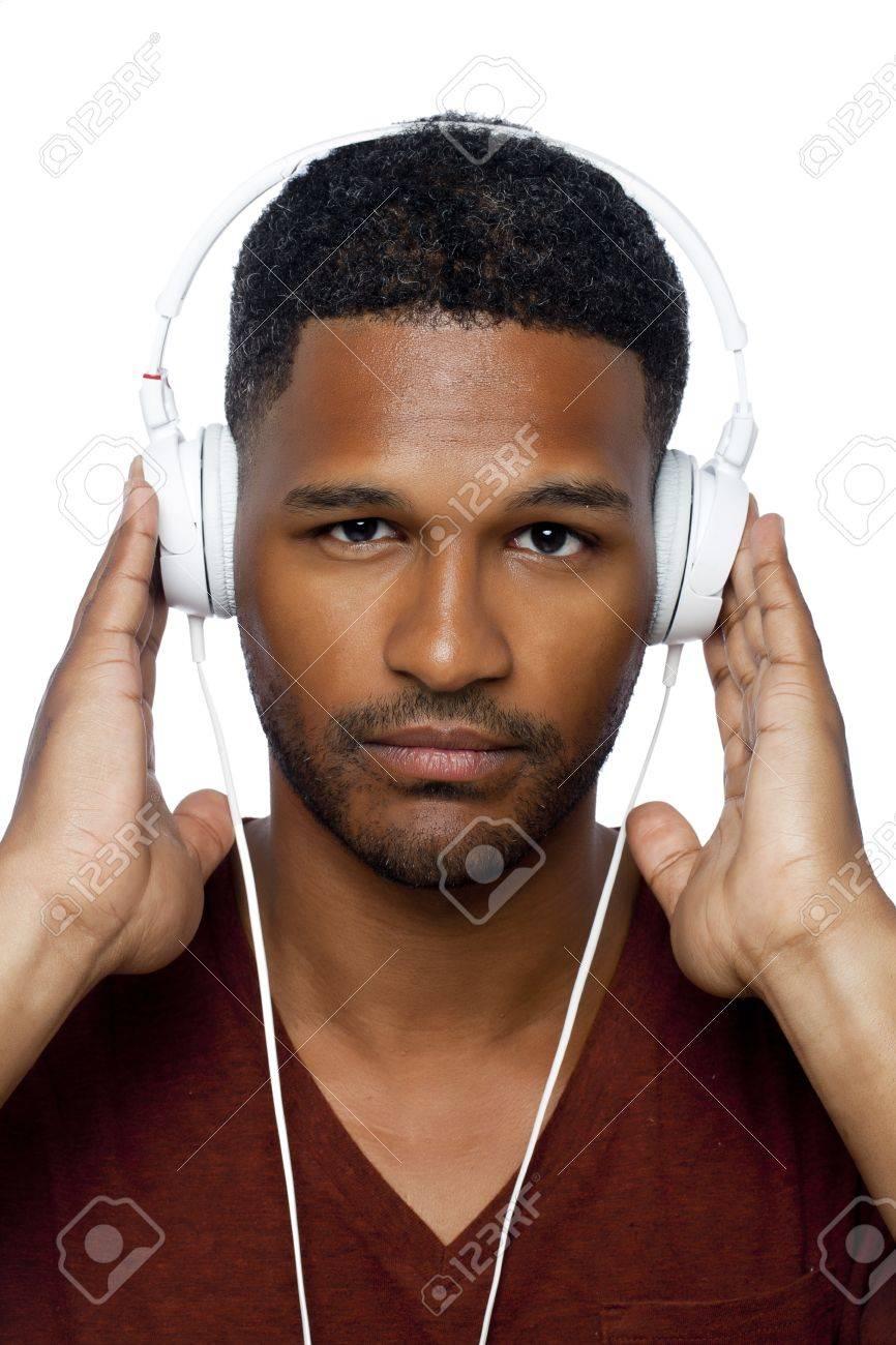 Portrait of dark guy with white headphone listening music against white background Stock Photo - 17521299