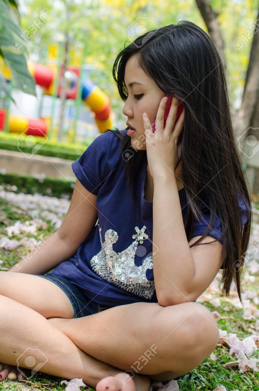 banque dimages belle fille chinoise en utilisant le tlphone cellulaire dans le graden