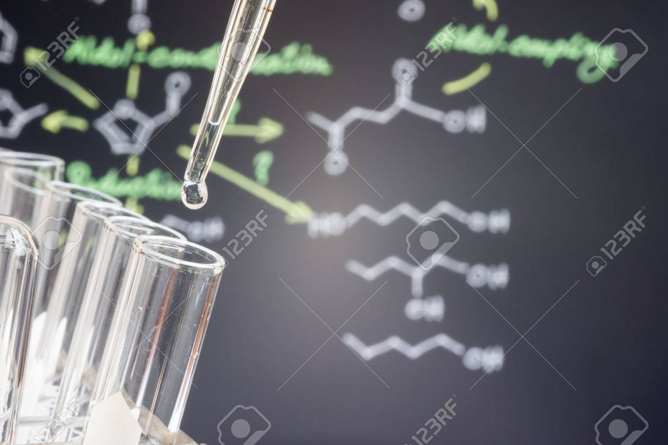 Reflection of chemical formular in water drop on test tube in front of blur chemical formula - 57553561