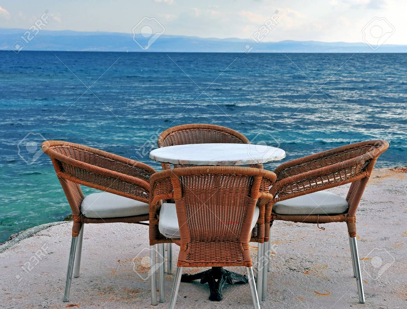 Stock Photo   Wooden Cafe Chairs And Table In Front Of Mediterranean Sea