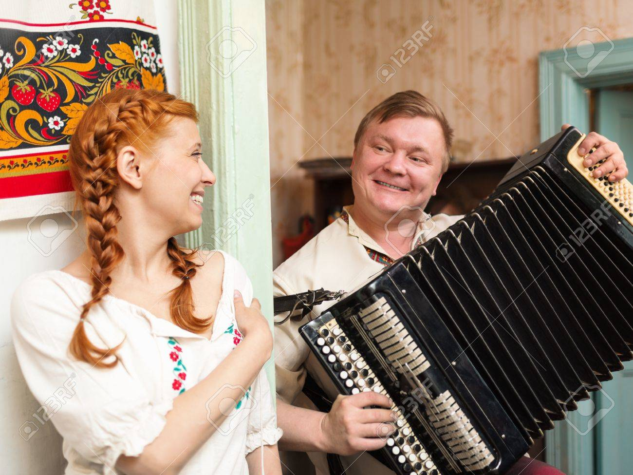 The girl near Russian stove and guy with an accordion