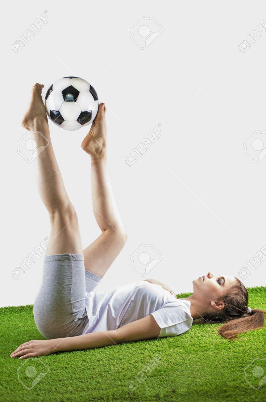 96d64a568029e Bonito fútbol femenino La mujer morena joven en ropa de deportes miente con  un balón de
