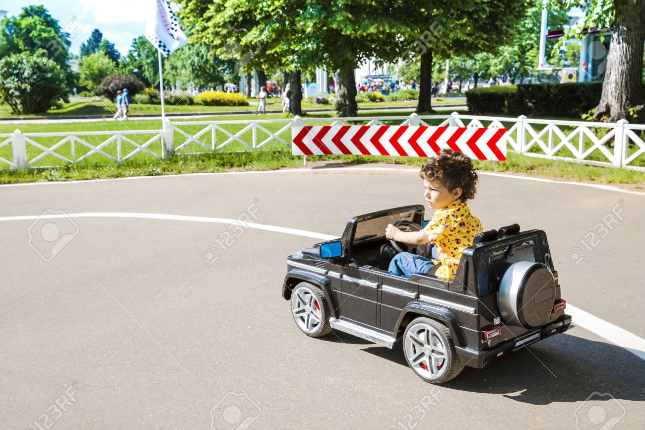 Amusement Park A Funny Boy Rides On A Toy Electric Car On A Stock Photo Picture And Royalty Free Image Image 99871254