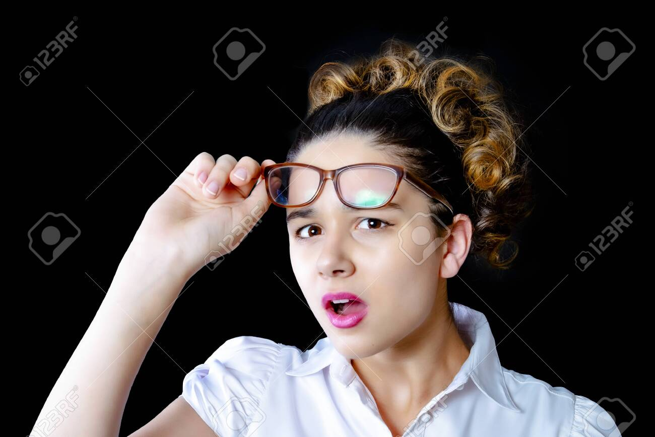 Surprised young female model with dark hair, wears glasses and a white blouse, looks with horror at the camera, notices something unexpected, hears bad news, is isolated from the black wall - 138967531