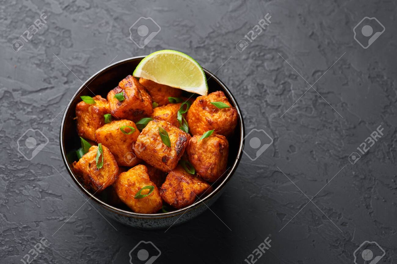 Paneer Manchurian or Paneer 65 in bowl at black concrete background. Paneer Manchurian is Indian Chinese cuisine dish with panner cheese, tomatoes, onion, soy sauce. Copy space - 130336645