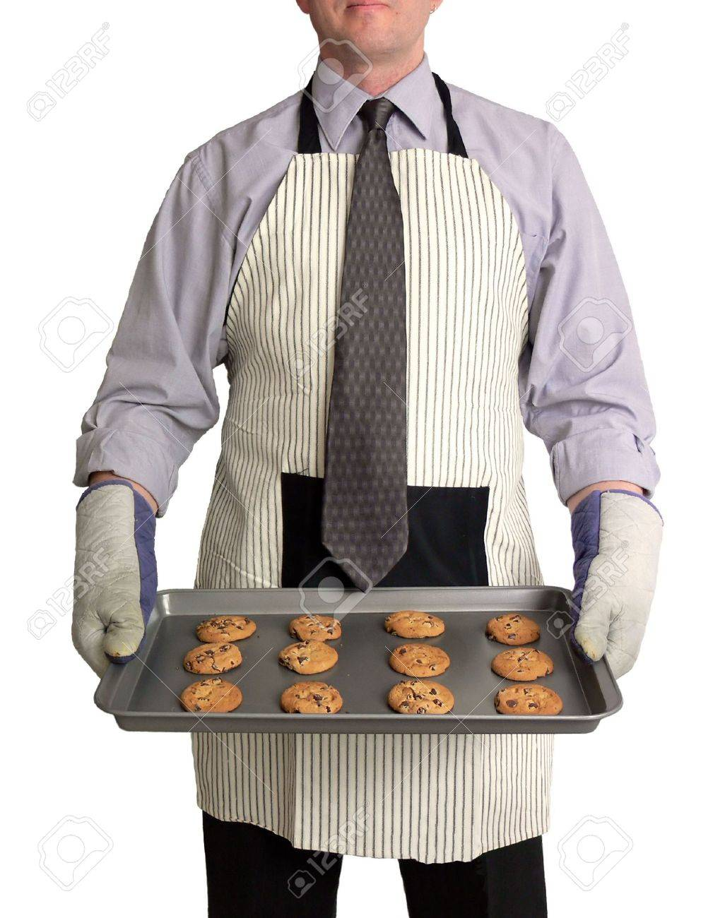 Image of a man against a white background, wearing a kitchen apron and oven mitts over business attire. He is holding a cookie sheet full of freshly-baked chocolate chip cookies in front of him. Stock Photo - 407670