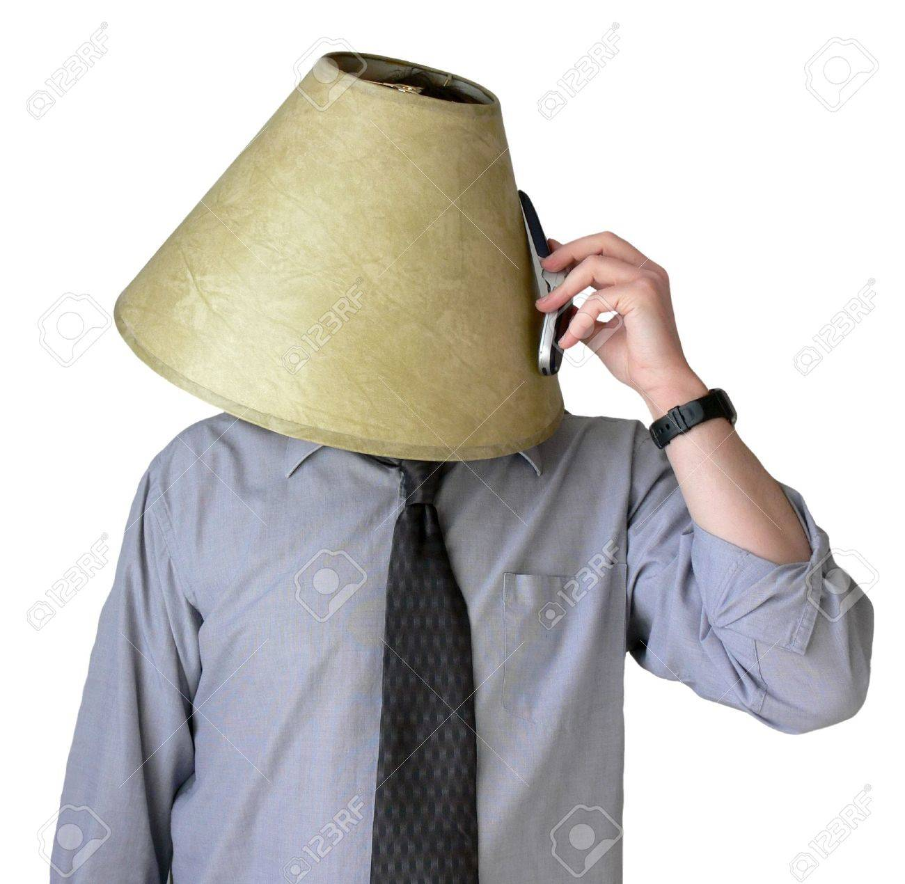 Businessman with a lampshade on his head, trying to talk on his cell phone. Stock Photo - 417672