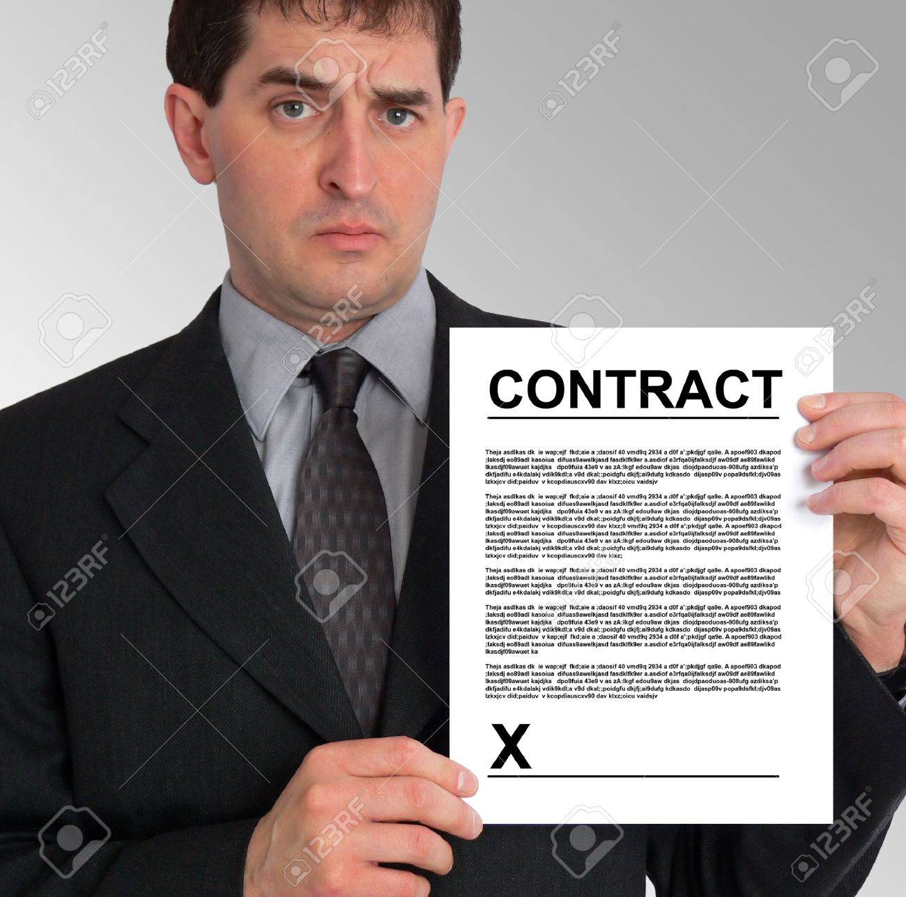 Image of a businessman holding a contract to his left, against a grey gradient background. Stock Photo - 417490