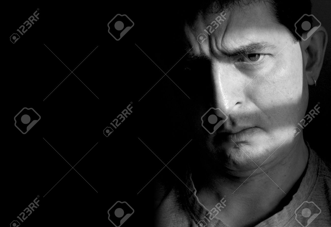 Black and white photo of a man with a furrowed brow and a doubtful look on his face. Half of the man's face is hidden in shadow, while the other half is in sunlight, with lighter bands of shadow across it. This photo was taken in my bathroom, with light c Stock Photo - 417481