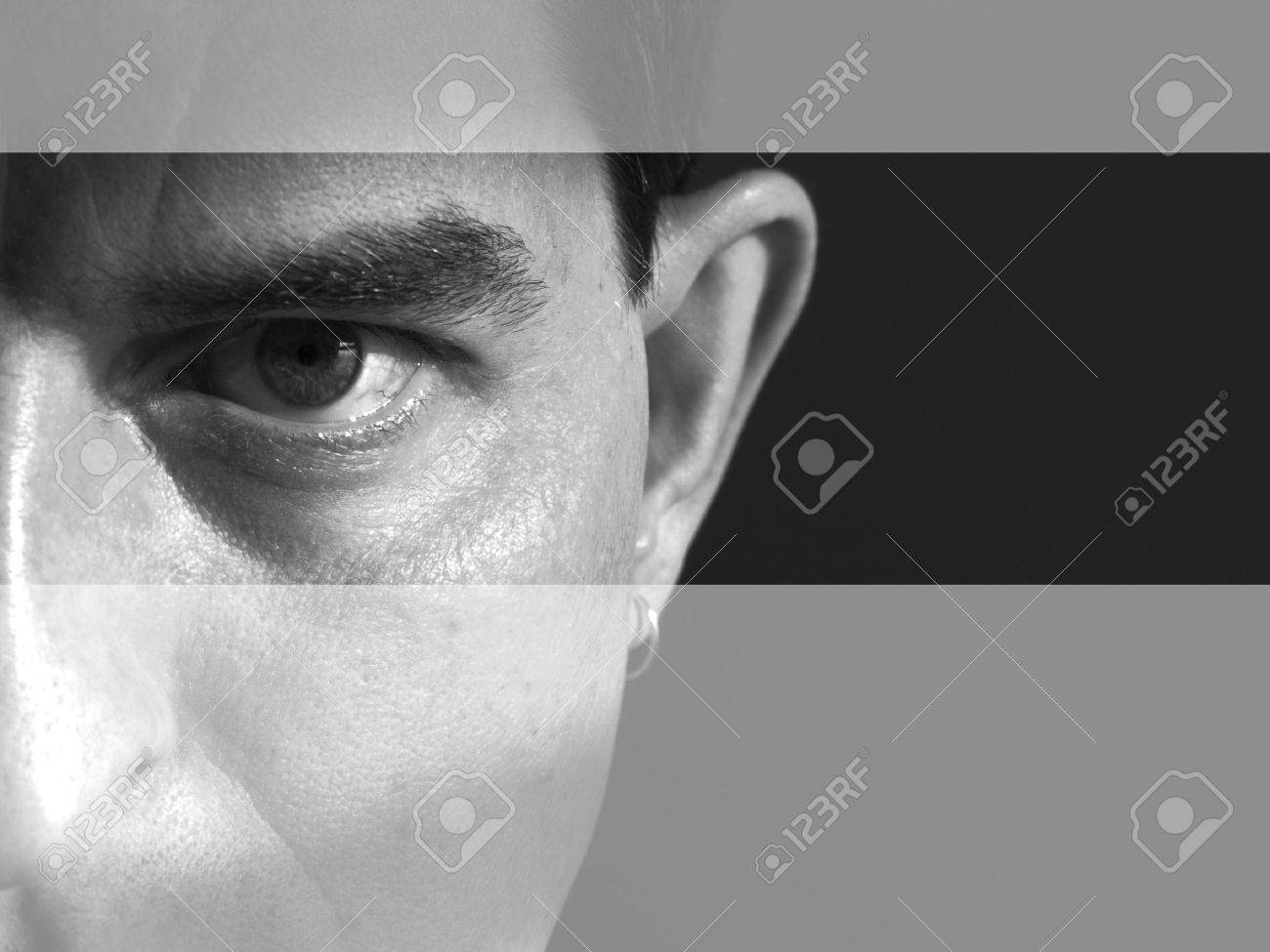 Black and white closeup of the left side of a man's face. Man is looking serious and intense and maybe angry. There are lighter bands going across the top and bottom of the image, drawing the viewer's eye to the model's eye.Taken in my bathroom with sunli Stock Photo - 417479