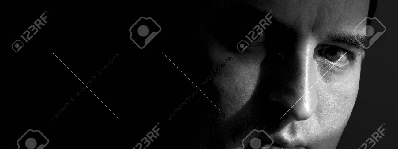 Black and white closeup of a man's face, with the right side mostly hidden in shadow. Image has a horizontal banner shape, with the face on the right and a background that varies from very dark grey to black. Man is looking serious and intense and maybe a Stock Photo - 417477