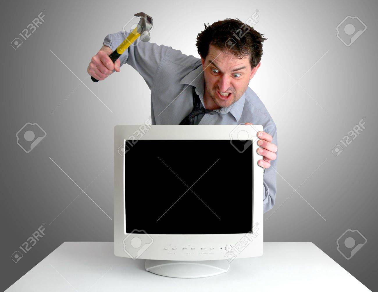 Tired, freaked-out business man preparing to smash a computer monitor with a hammer. Stock Photo - 417489