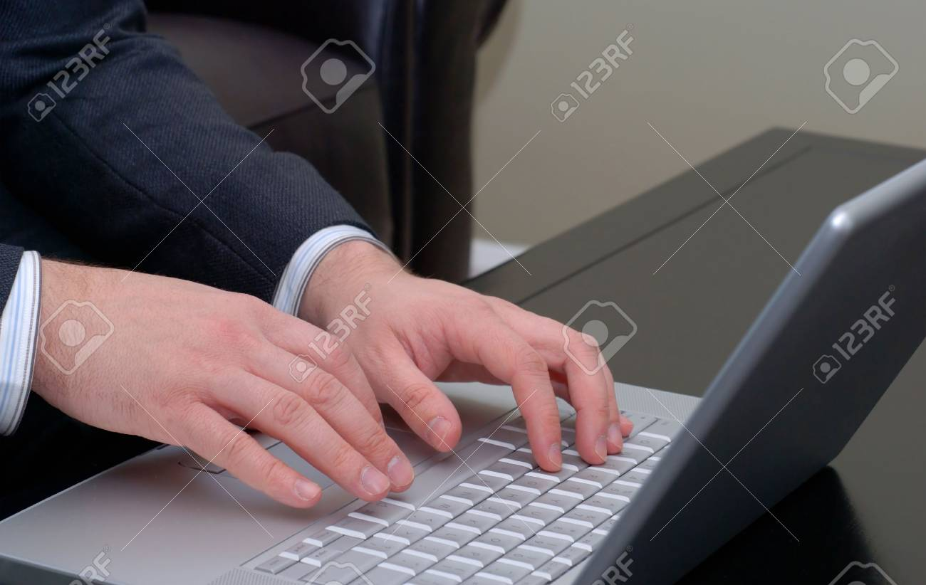 Businessman's hands on the keyboard of a silver laptop computer. Stock Photo - 759877