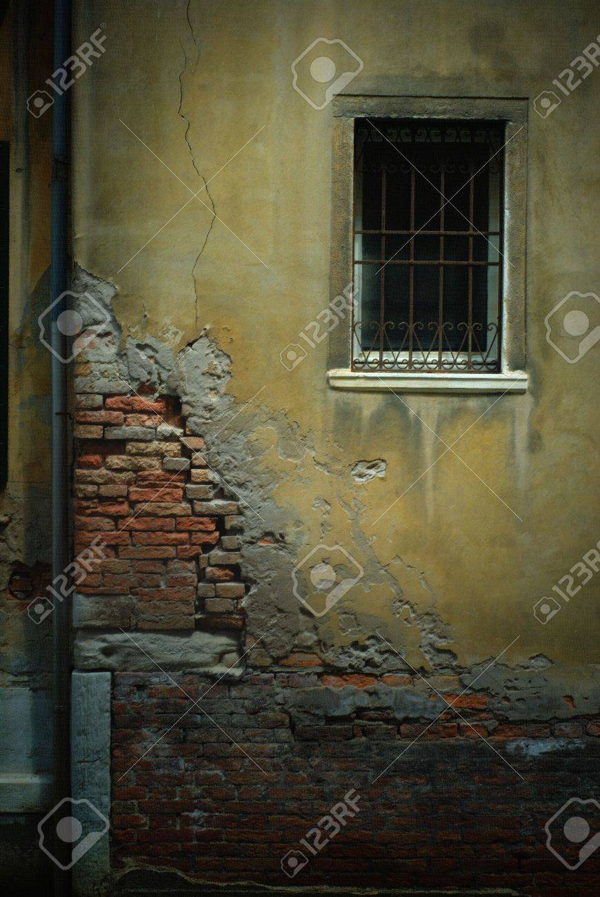 Crumbling wall in Venice, Italy, with exposed brick, a barred window and a pipe. Image has a light pastel on canvas effect added to it. Stock Photo - 1780809