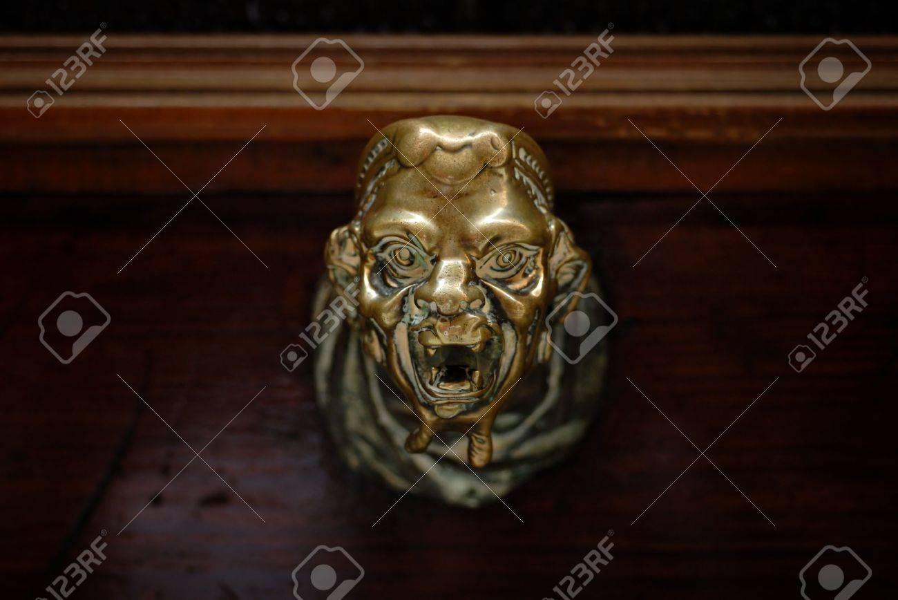 Creepy Head Shaped Brass Doorknob On Dark Wooden Door In Venice