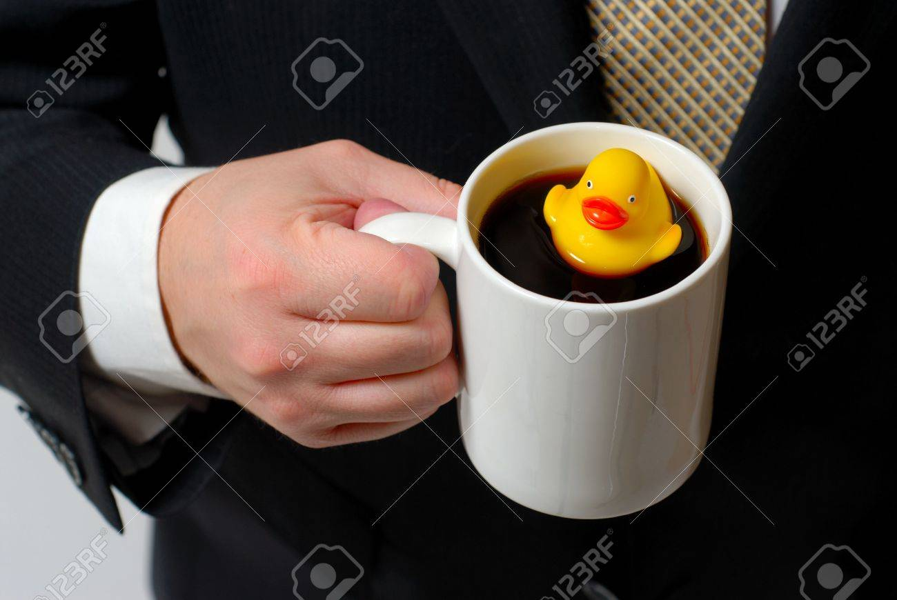 Yellow rubber ducky floating in a coffee cup being held by a man in a business suit. Stock Photo - 4391686