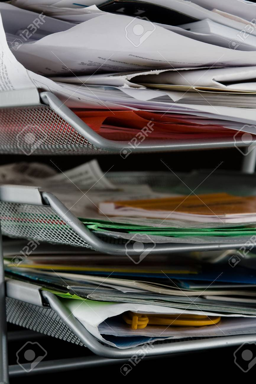 In-basket overflowing with papers,mail and other documents. Isolated on black background. Stock Photo - 2450505