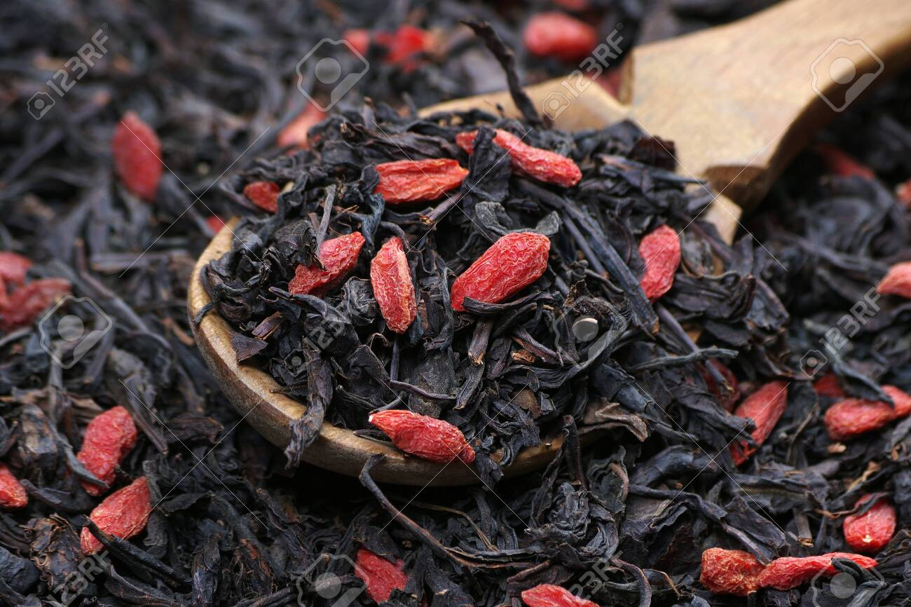 Black Tea Leaves And Goji Berries In A Wooden Spoon Black Blended