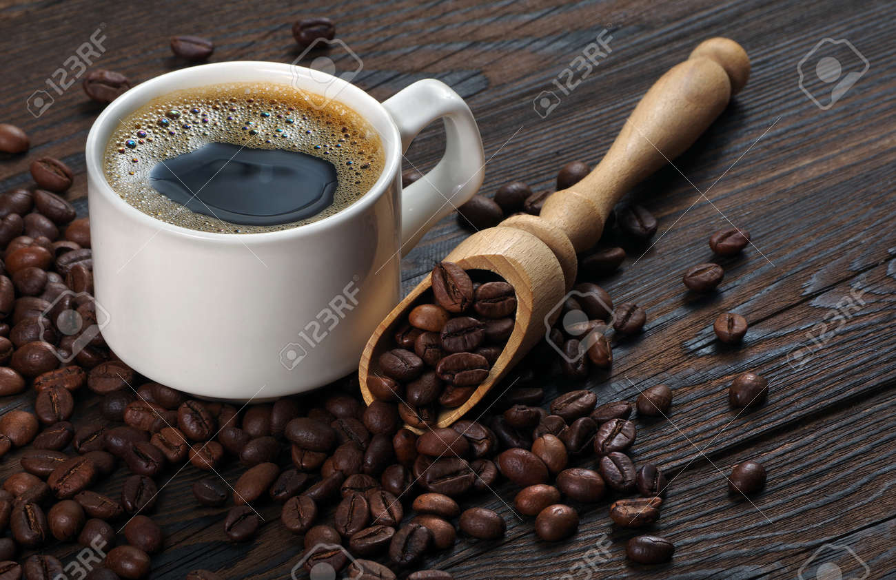 Coffee beans and cup of coffee on a wooden table. coffee in a white cup. - 157013959