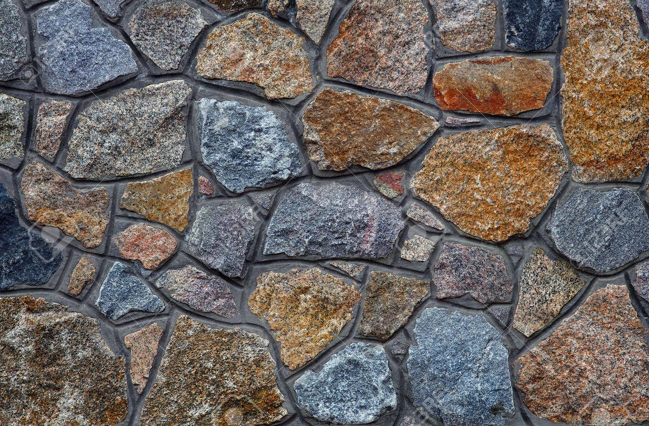 stone wall. wall of granite blocks. a masonry wall of multicolored stones or blocks close up - 169620125