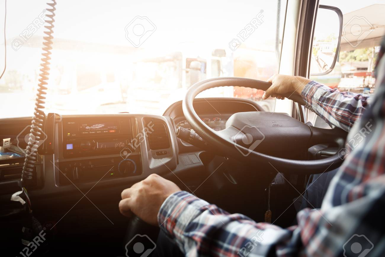 Truck driver keeps driving with one hands and change gears,The man Behind Semi Truck Steering Wheel,spot focus. - 126512448