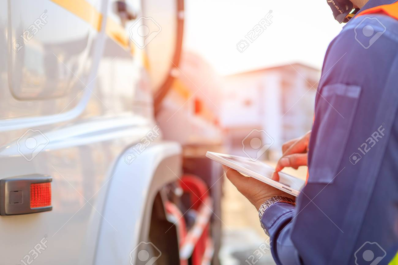 Truck drivers hand holding tablet checking the product list,Driver writing electronic log books,spot focus. - 126512462